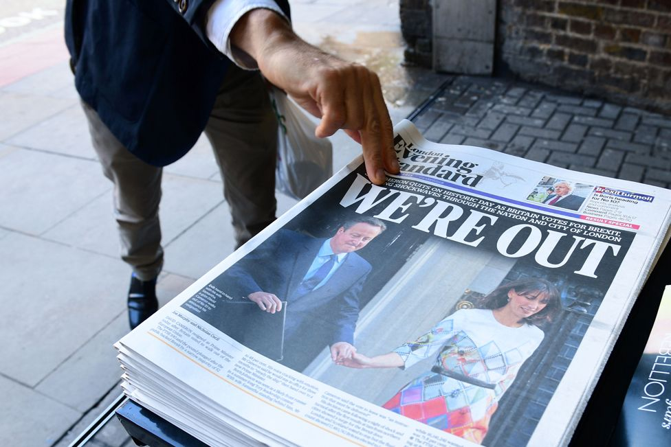 A man takes a copy of the London Evening Standard with the front page reporting the resignation of British Prime Minister David Cameron and the vote to leave the EU in a referendum, showing a pictured of Cameron holding hands with his wife Samantha as they come out from 10 Downing Street,