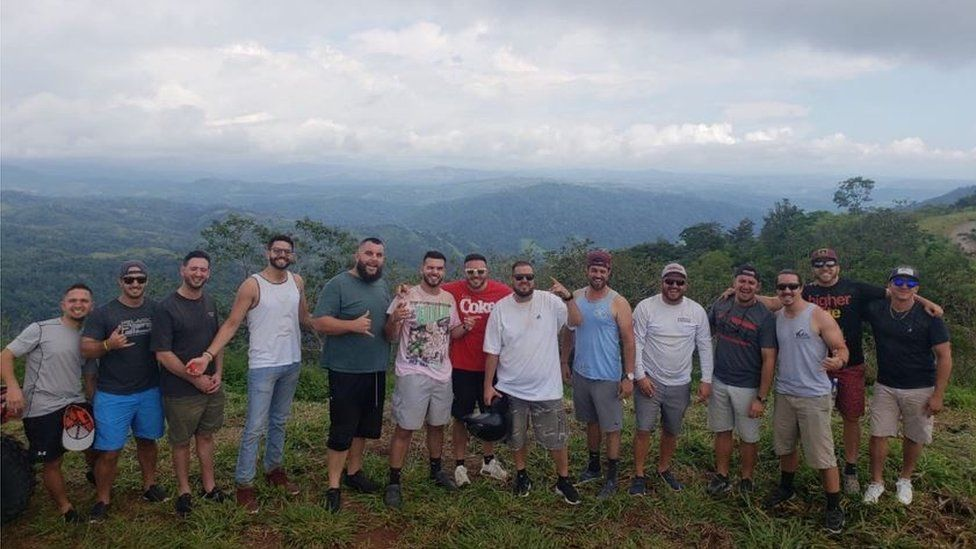The group of 14 friends pose for a photo in the Costa Rican mountains