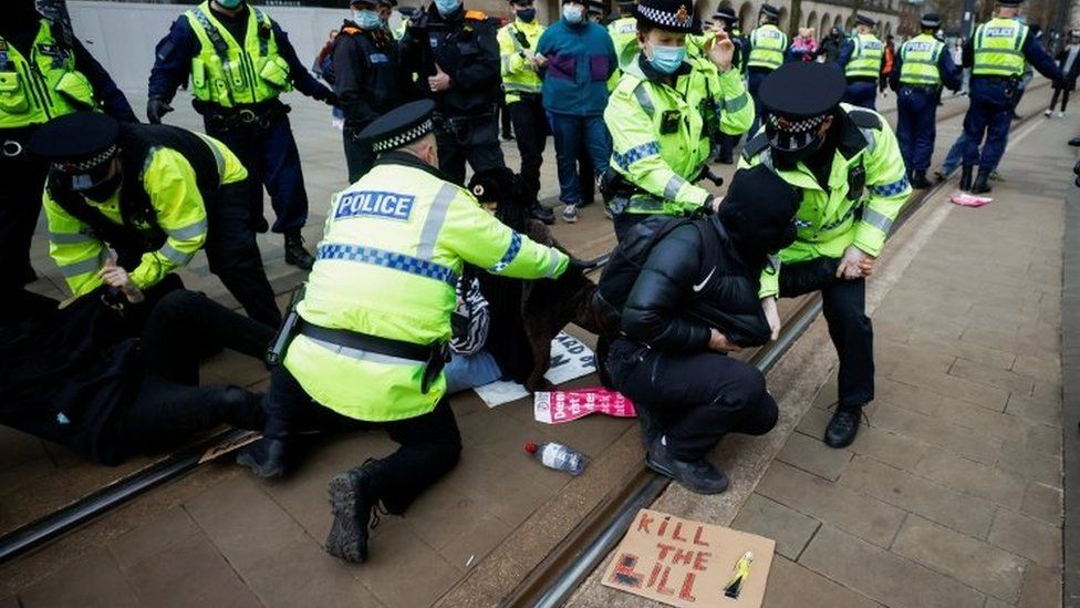 Police officers detain a demonstrator during a protest in Manchester