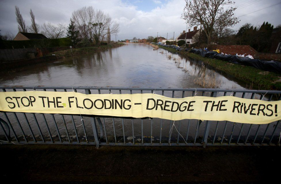 A protest banner is displayed on the road bridge crossing the River Parrett at Burrow Bridge in January 2014 in Somerset,