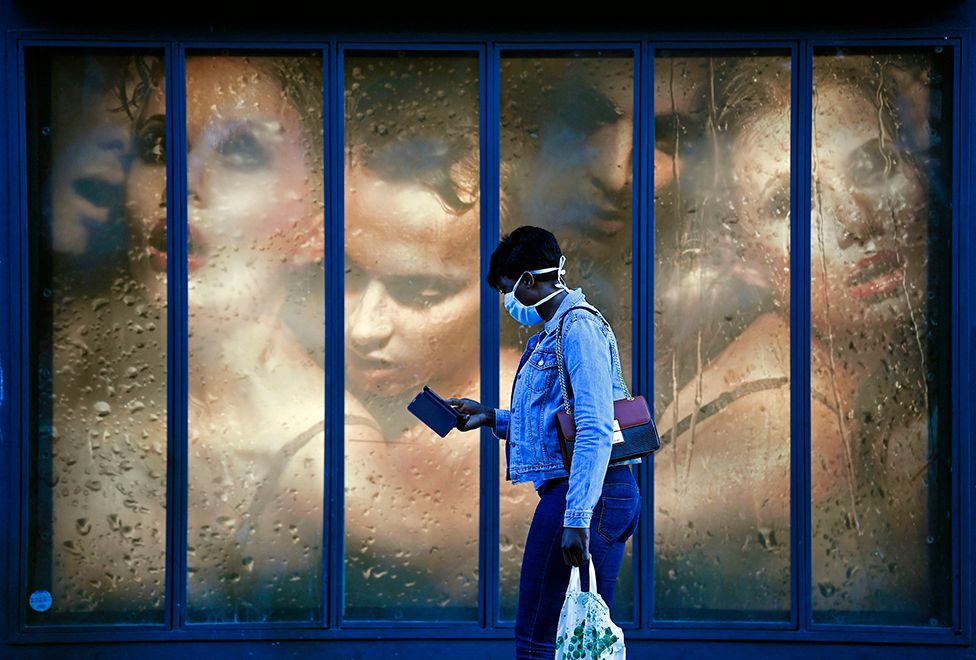 A woman wearing a protective mask walks past a store window with an advert behind her showing lots of women crowded together