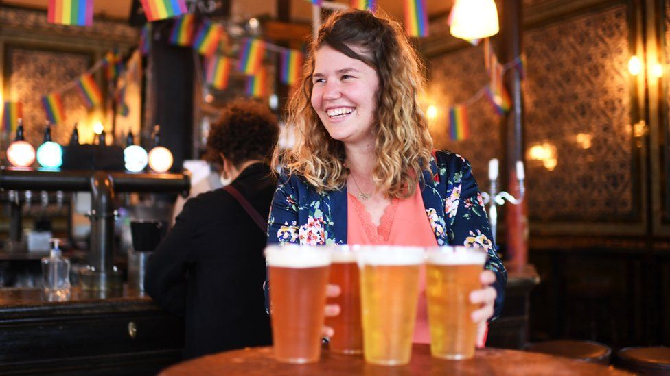 A young woman smiles while holding pints of beer in a pub