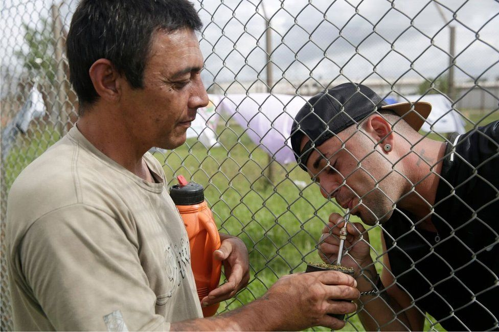 Two men drink a mate tea through a fence at Punta de Rieles jail