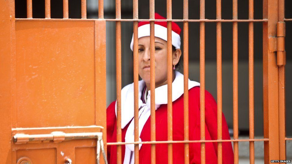 A woman in a Santa outfit standing in prison