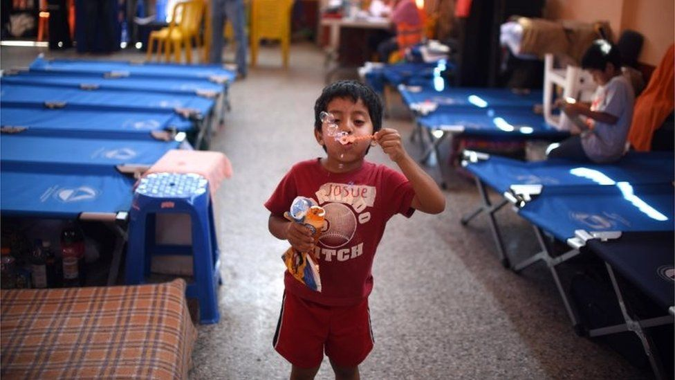 A child plays in a makeshift shelter in Santa Catarina Pinula on 6 October, 2015