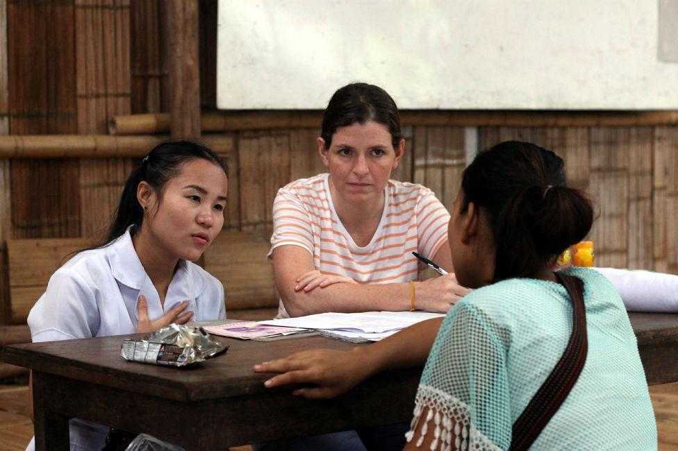 Gracia Fellmeth and a colleague talks to a young woman in Mae La
