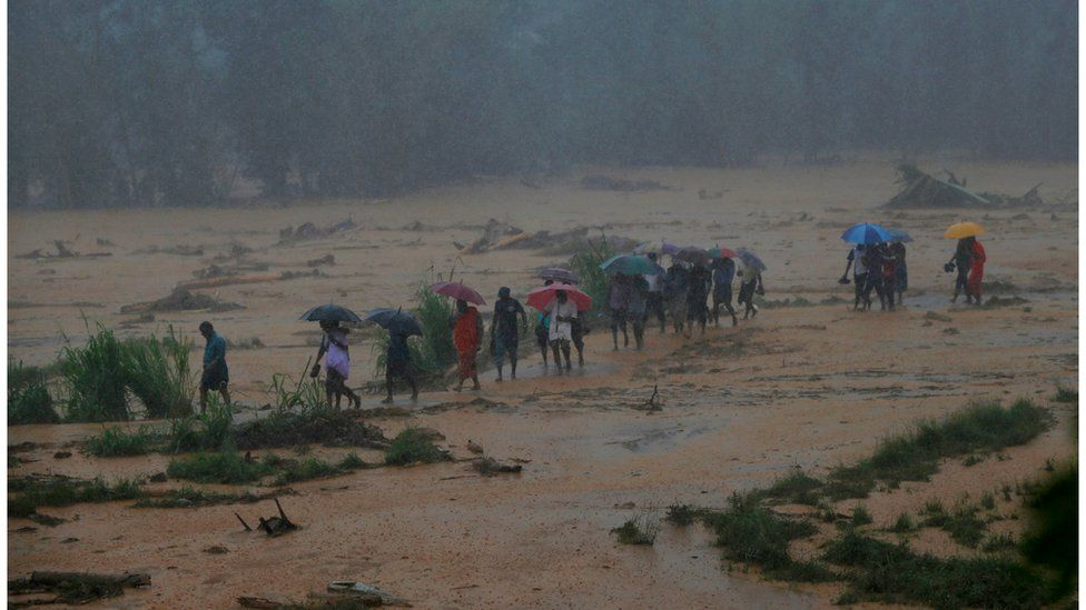 Villagers walk through rain, mud and ankle-deep water, after the landslide. Photo taken 18 May 2016.