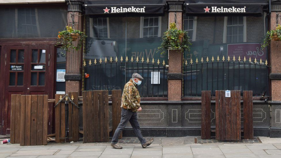 A man wearing a protective face mask walks past a closed pub in central London