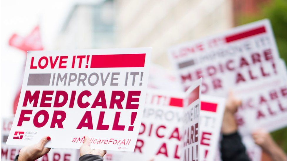 """Members of National Nurses United union members wave """"Medicare for All"""" signs during a rally in front of the Pharmaceutical Research and Manufacturers of America in Washington calling for """"Medicare for All"""" in April 2019"""