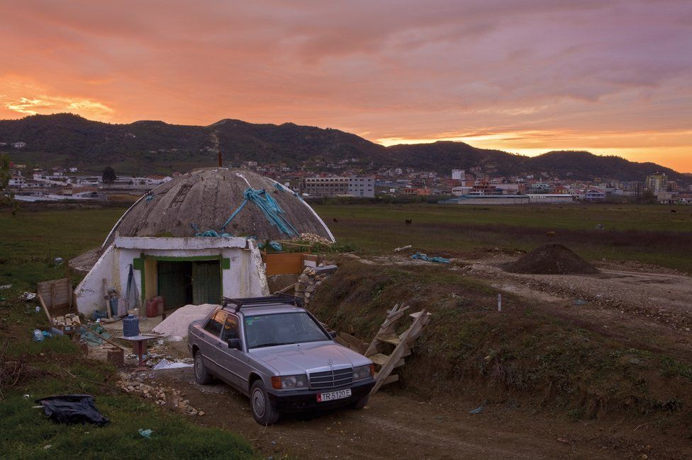 Bunker in Albania with a car next to it and buildings in the background