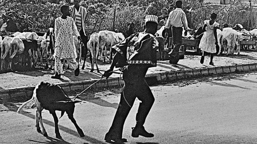 "A photo by Sunmi Smart-Cole entitled: ""Christmas Dinner""- Monday 25 December 1978, showing a man pulling a goat with a rope"
