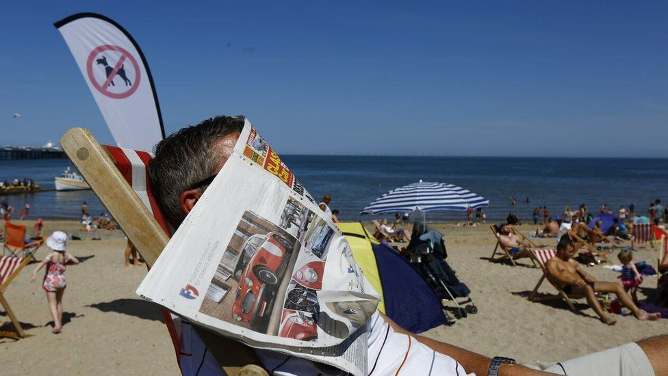 Man sunbathing with paper over his face