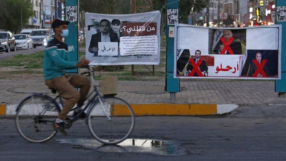 """A man rides his bicycle past a banner in Karbala reading in Arabic """"Who killed me?"""" and depicting renowned Iraqi anti-government activist Ehab al-Wazni, who was shot dead (23 May 2021)"""