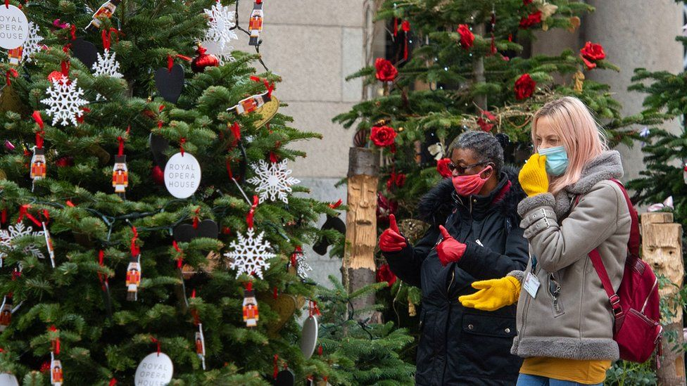 Woman in face masks looking at Christmas trees