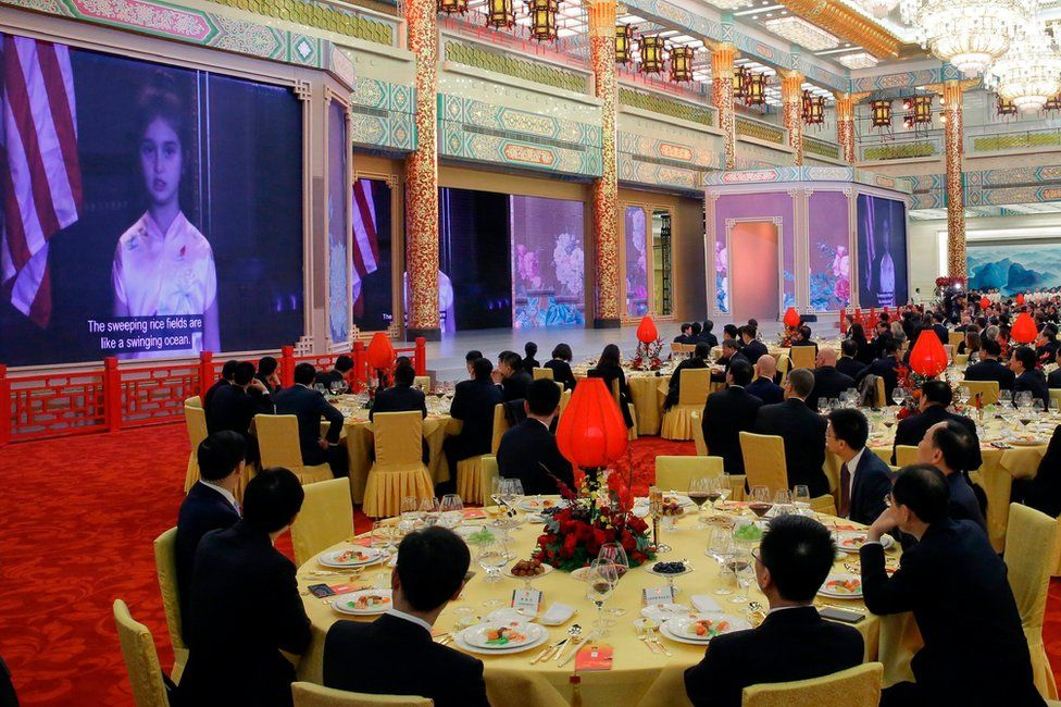 Guest watch a video of Arabella Kushner, granddaughter of US President Donald Trump, sing a traditional Chinese song during a state dinner at the Great Hall of the People in Beijing on 9 November 2017