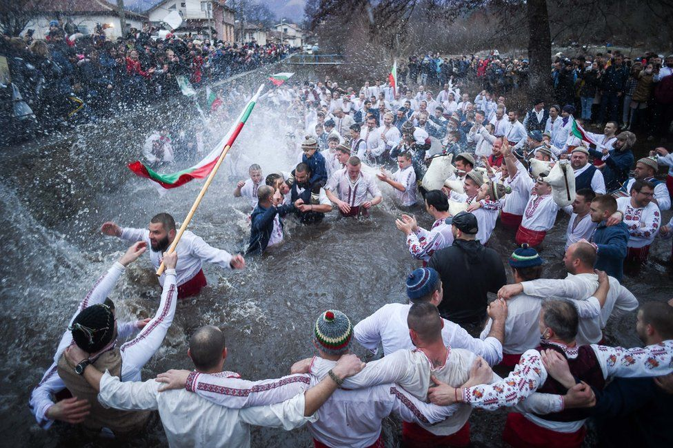 "Bulgarian men perform the traditional ""Horo"" dance in the icy winter waters of the Tundzha river in the town of Kalofer, as part of Epiphany Day celebrations on 6 January 2021."