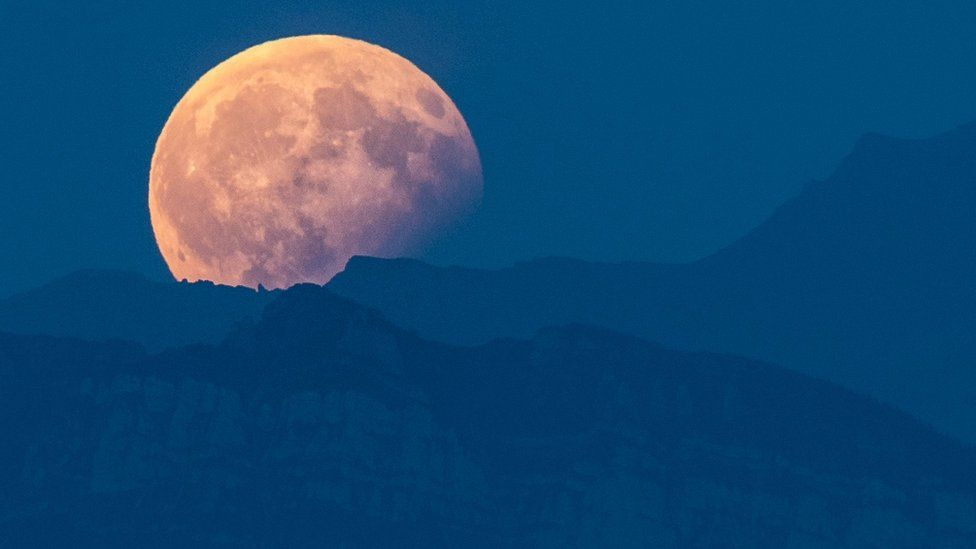 The full moon is seen during a partial lunar eclipse above the Bernese Alps, from Bern, in Switzerland, 07 August 2017.