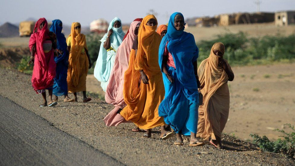 A group of women in colourful clothing walking in a line on the side of a road. They are on a dirt pavement. They are wearing traditional long dresses with hijabs. Their surroundings look rural.