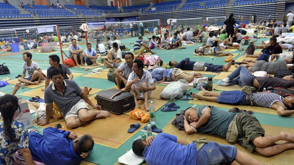 Chinese workers rest at Nansha Stadium as Typhoon Nida hit the area in Guangzhou