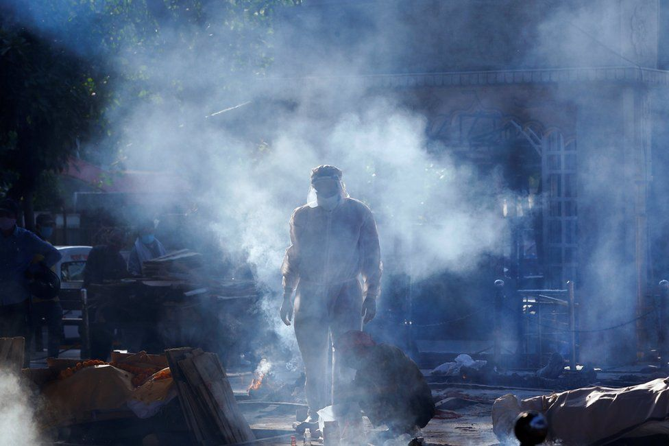 A family member wearing personal protective equipment (PPE) stands next to a body of a person in crematorium as smoke hangs in the air