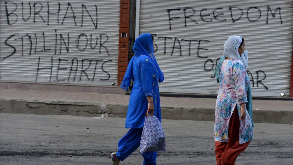 Women walk past a shuttered shop with pro-militant slogans spray painted on