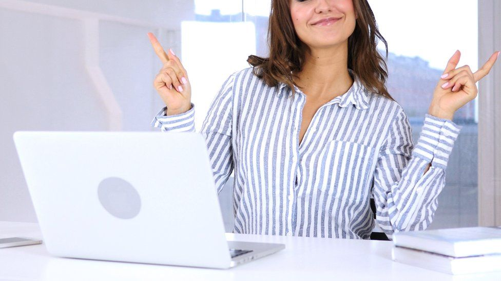 A stock image of a woman smiling and dancing in front of her computer