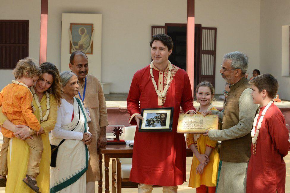 Mr Trudeau (C) poses with his family and a trustee of the Sabarmati Ashram in Ahmadabad, Gujarat.