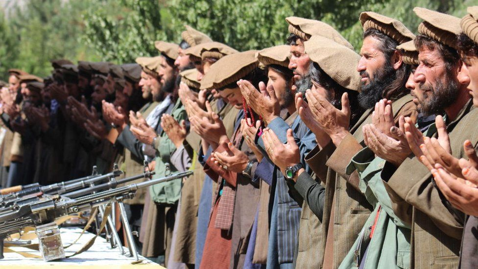 A group of Taliban soldiers praying after sacrificing their weapons and joining the Afghan government
