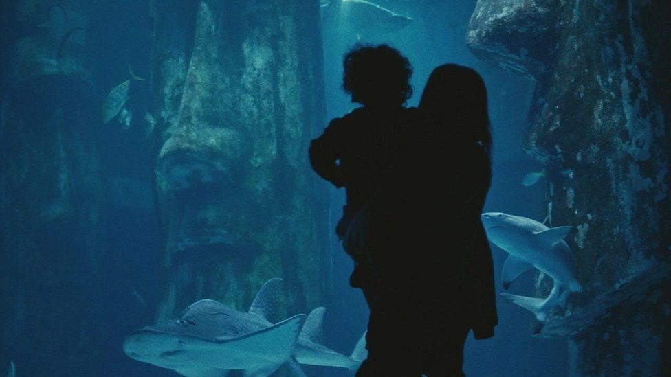 Woman holding child in front of tank of sharks.