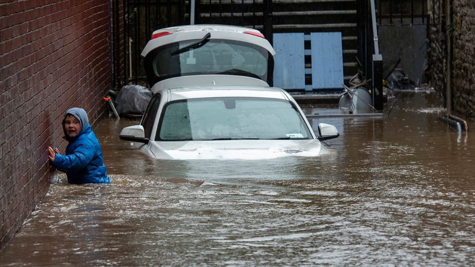 A boy wades towards a flooded alleyway in Pontypridd on Sunday