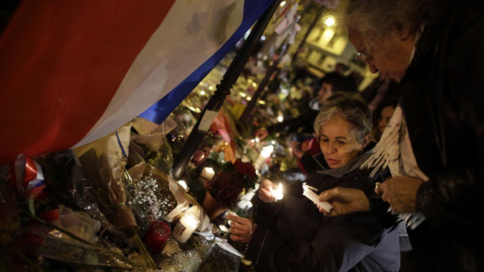 Women light candles in front of a memorial set up outside the La Casa Nostra restaurant