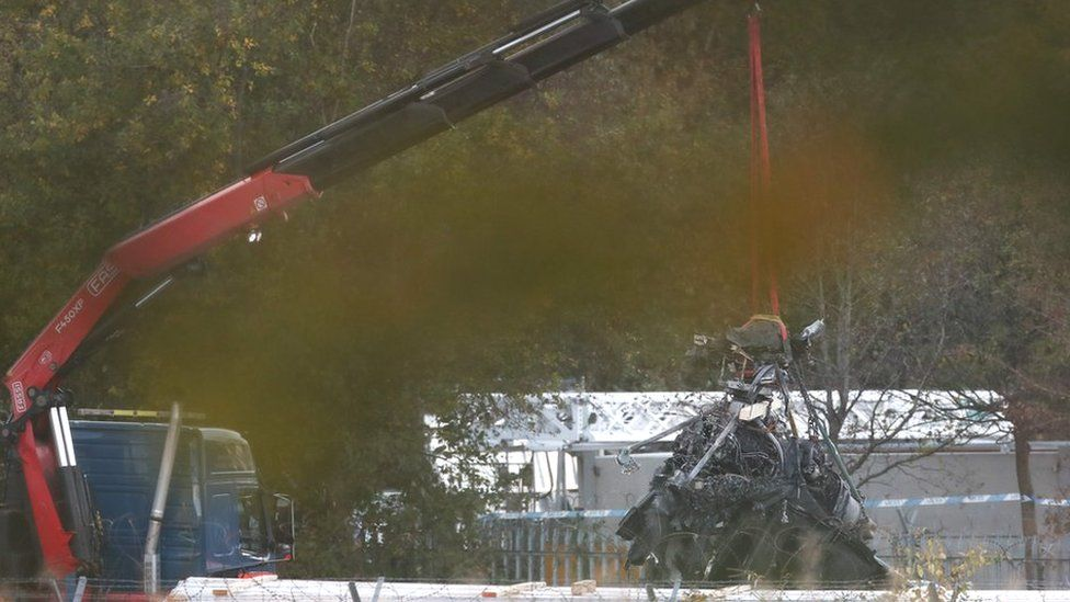 Part of what remains of the helicopter which crashed outside the King Power Stadium lifted by a crane