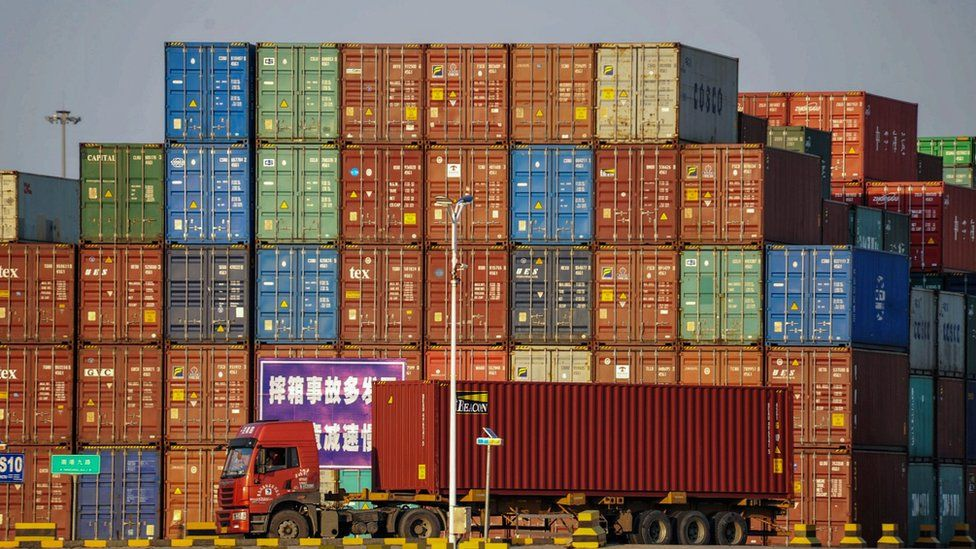 A truck transports a container next to stacked containers at a port in Qingdao in China's eastern Shandong province on October 12, 2018.