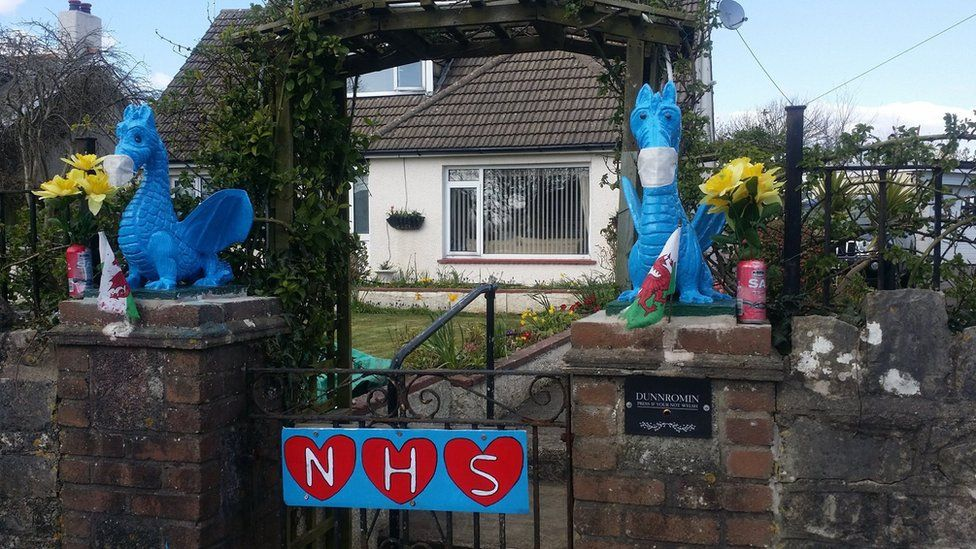A gate with dragons dressed to look like frontline workers and a sign reading NHS decorated with hearts