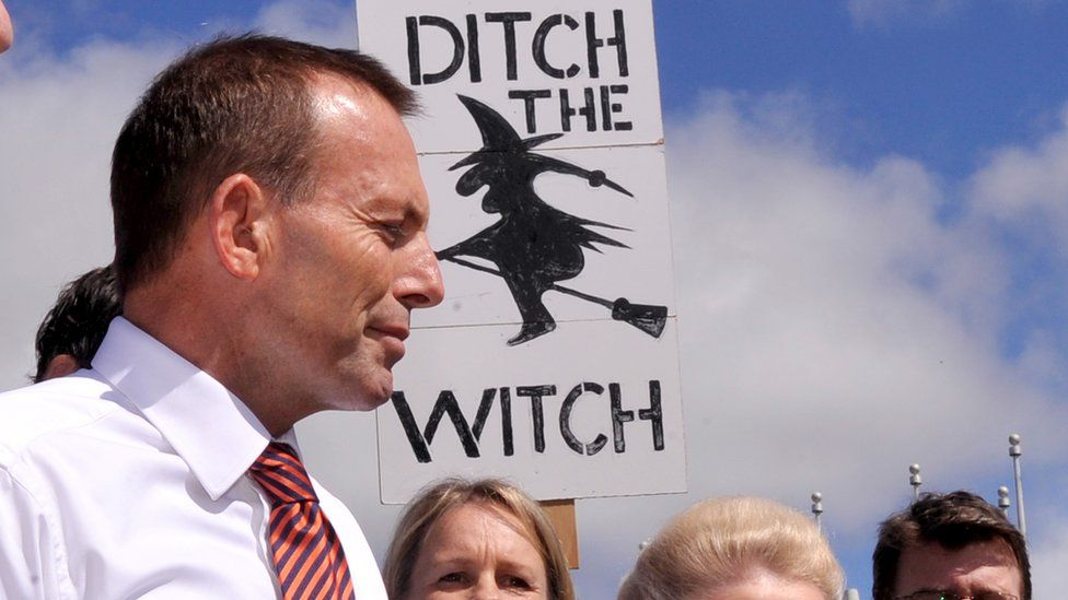 """Australia's then opposition leader, Tony Abbott, stands in front of a sign being held held by a protester in 2011. The sign reads: """"Ditch the witch""""."""