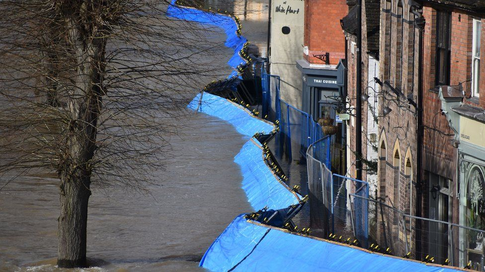 Temporary flood barriers which have been moved by the River Severn towards the Wharfage in Ironbridge