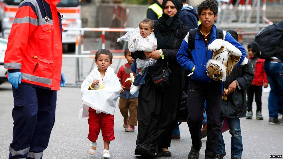 Migrants makes their way to wait for buses after arriving by train at the main railway station in Munich, Germany (September 7, 2015)