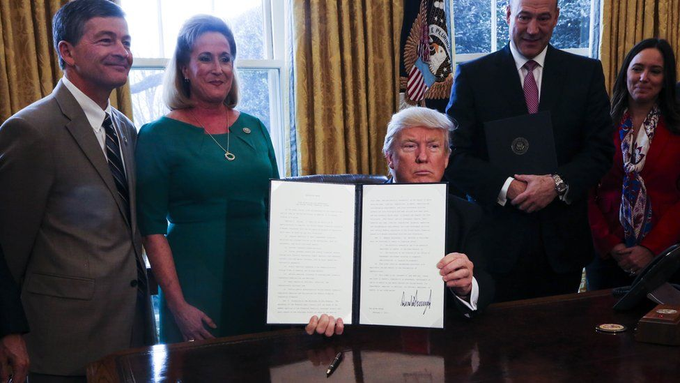US President Donald Trump signs an order asking for review of Dodd-Frank