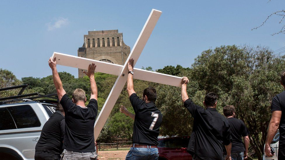 White South African activists haul a white cross aloft from the back of a jeep - to protest a rise in farm murders in the country.