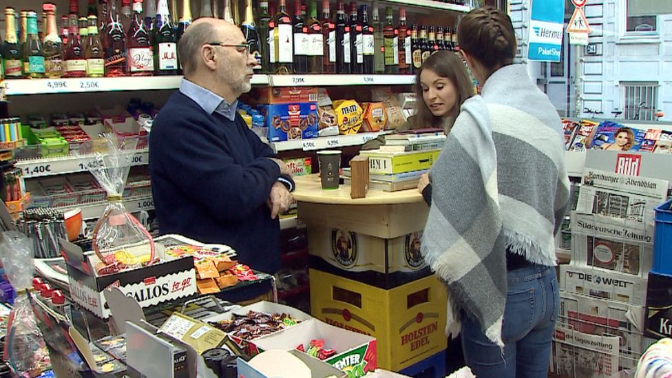 Michael Sachs and Anne Marie Hovingh stand in a Hamburg shop with newspapers and other products on the shelves