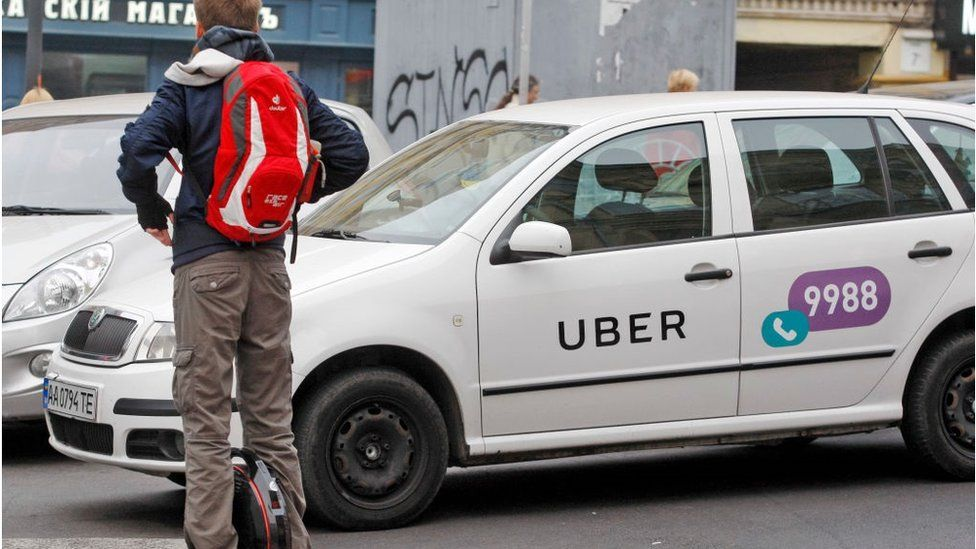 :A man seen on an electric unicycle at a crosswalk in front of a white car with a logo of Uber taxi cab company in Kiev, Ukraine