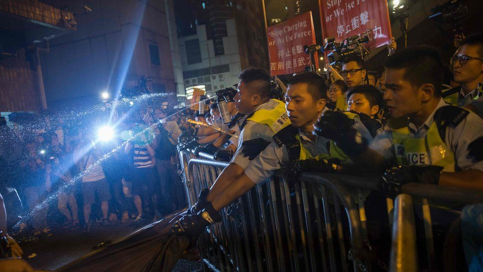 """Police use pepper spray to stop protesters charging outside the Chinese Liason Office in Hong Kong on November 6, 2016, during a protest against an expected interpretation of the city""""s constitution - the Basic Law - by China""""s National People""""s Congress Standing Committee"""