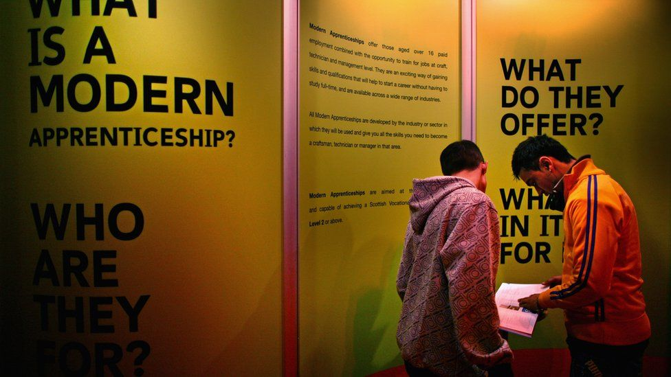 Young men next to a stand with information about apprenticeships