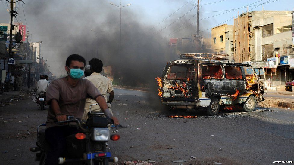 Pakistanis ride past a burning vehicle in Karachi following the arrest of Altaf Hussain in London.
