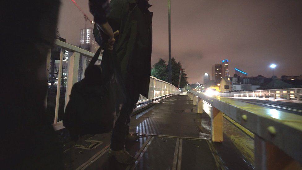 Man with money bag on bridge