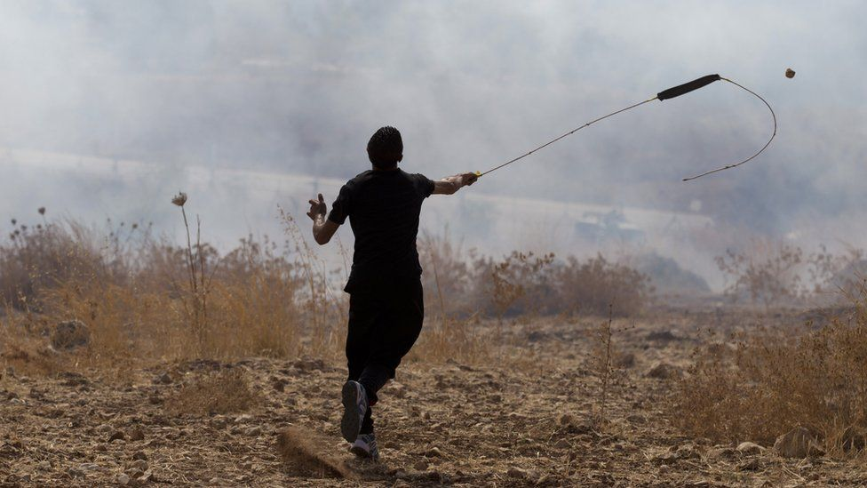 A Palestinian protester uses a slingshot to hurl a stone towards Israeli forces in the occupied West Bank (2 October 2105)