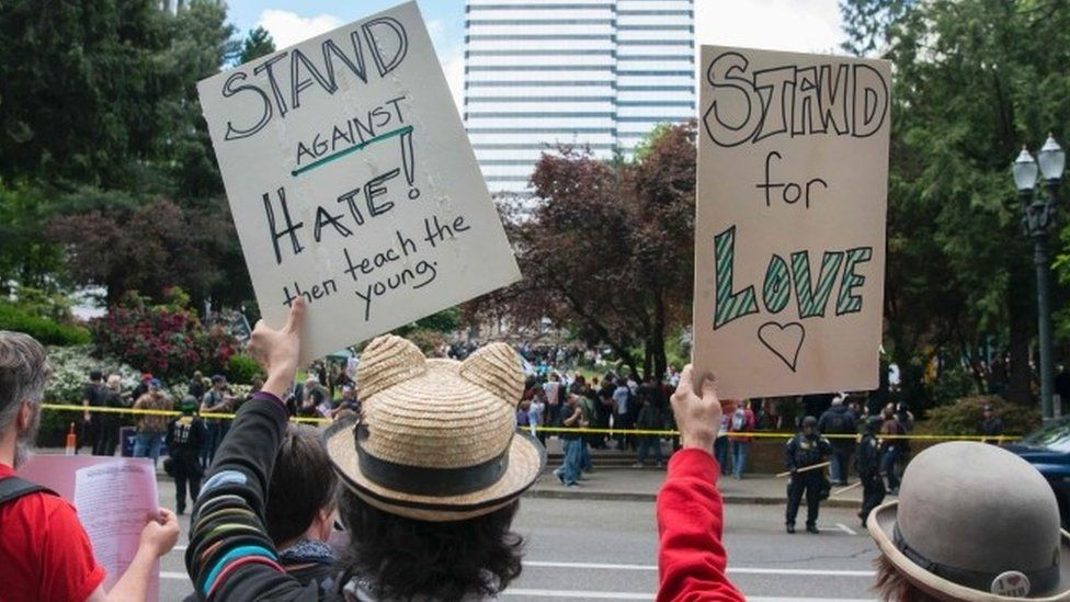Anti-Trump demonstrators hold signs up across the street from a pro-Trump rally in Portland (05 June 2017)
