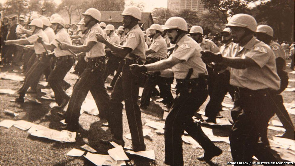 Policeman advancing against protestors during the 1968 Democratic National Convention in Chicago.
