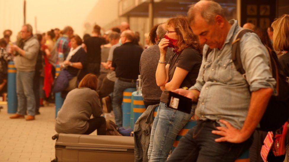 Stranded passengers wait at Las Palmas Airport in Gran Canaria, as a sandstorm disrupts travel