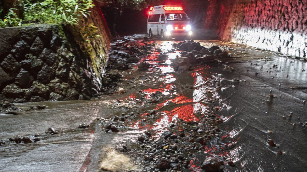 An emergency vehicle drives through debris on a flooded road during the evacuation of guests at the Osen Sanso Nakamura hotel in Sengokuhara, in Nakone province, Japan, 12 October 2019.